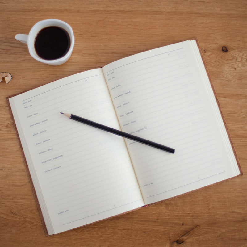 photo-of-open-day-planner-with-pencil-on-top-and-cup-of-coffee-nearby