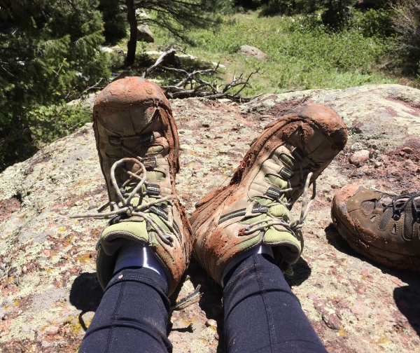 muddy-hiking-boots-on-feet-of-hiker-sitting-on-large-rock