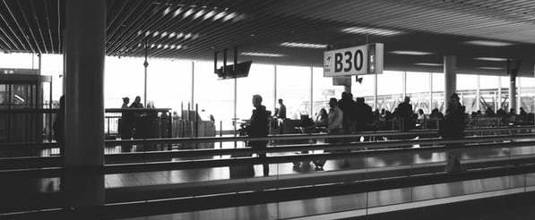 black-and-white-photo-of-people-sitting-and-standing-at-airport-gate-B30