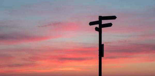 roadsigns-pointing-different-directions-at-golden-hour