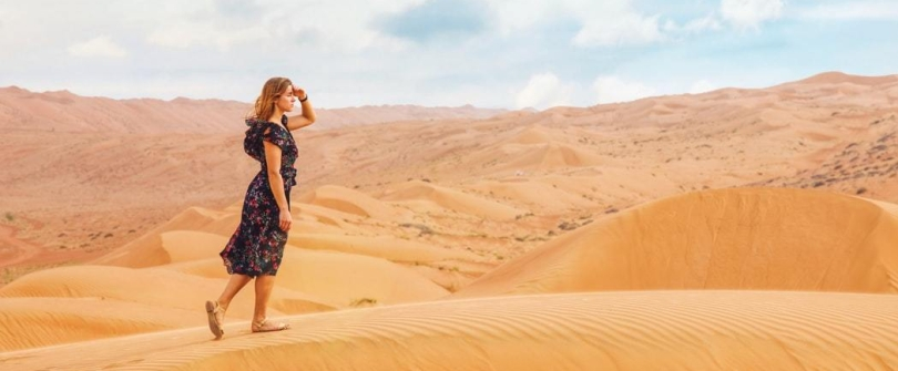 woman wearing floral dress blocking sun with hand while walking on sand dune in desert