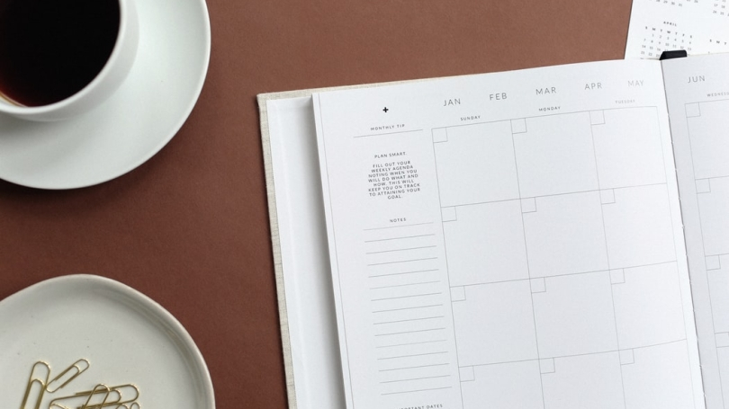 yearly calendar on table with cup of coffee and dish of paper clips