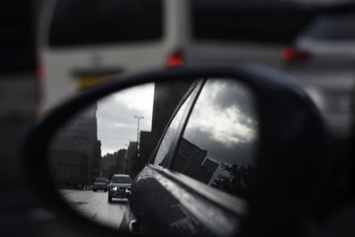car side mirror with city and other cars in reflection