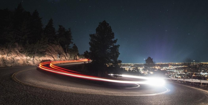 nighttime time lapse of mountain road curving and car lights driving around pine tree