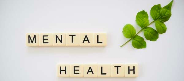 scrabble tiles reading Mental Health with sprig of greenery on side