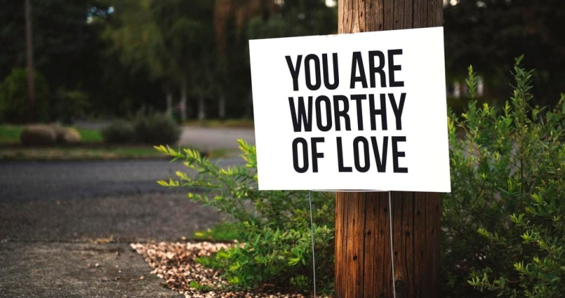 """white sign with black capital letters reading """"you are worthy of love"""" near telephone pole, green bush, and asphalt walkway"""