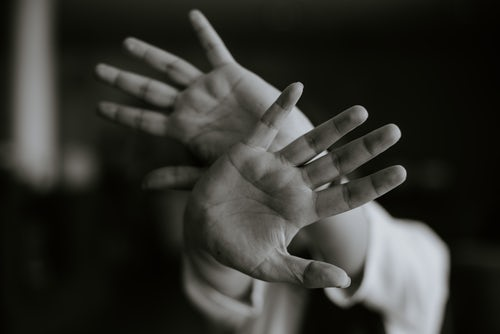 person-extending-hands-with-open-palms-in-stop-gesture-as-contamination-ocd-concept-in-black-and-white