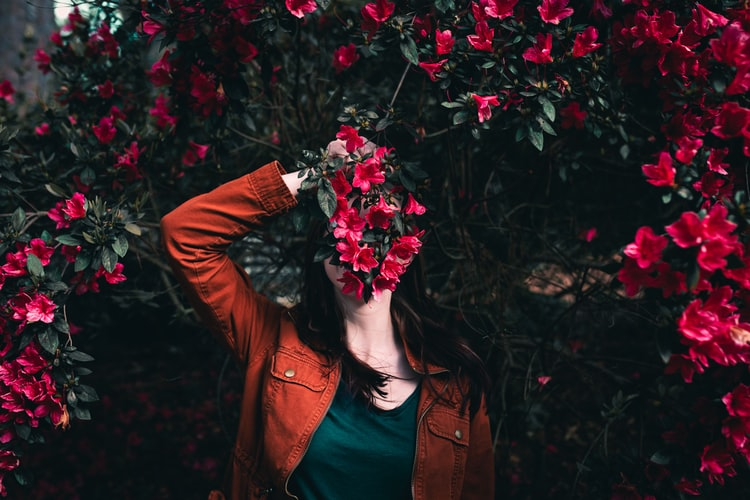 woman in orange jacket holding flowers in front of face