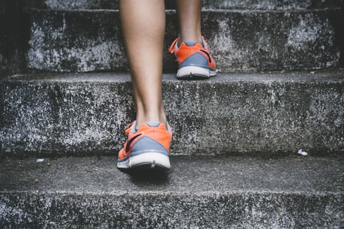 woman running shoes running up concrete staircase