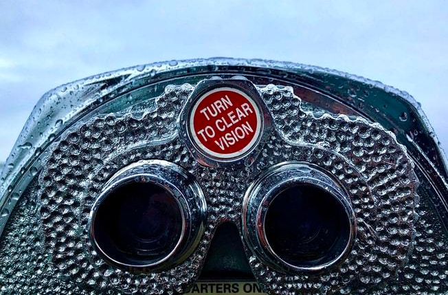 coin-operated-binoculars-with-raindrops-on-surface-and-red-knob-reading-turn-to-clear-vision