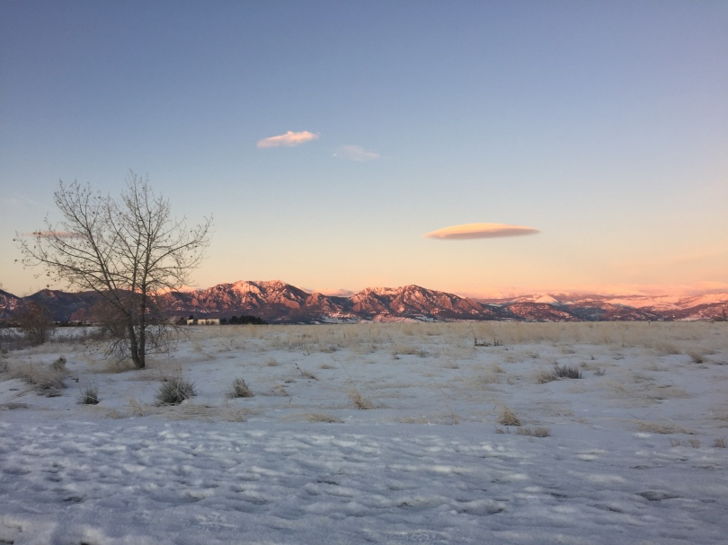 blue and pink mountains illuminated by sunrise over snowy plains