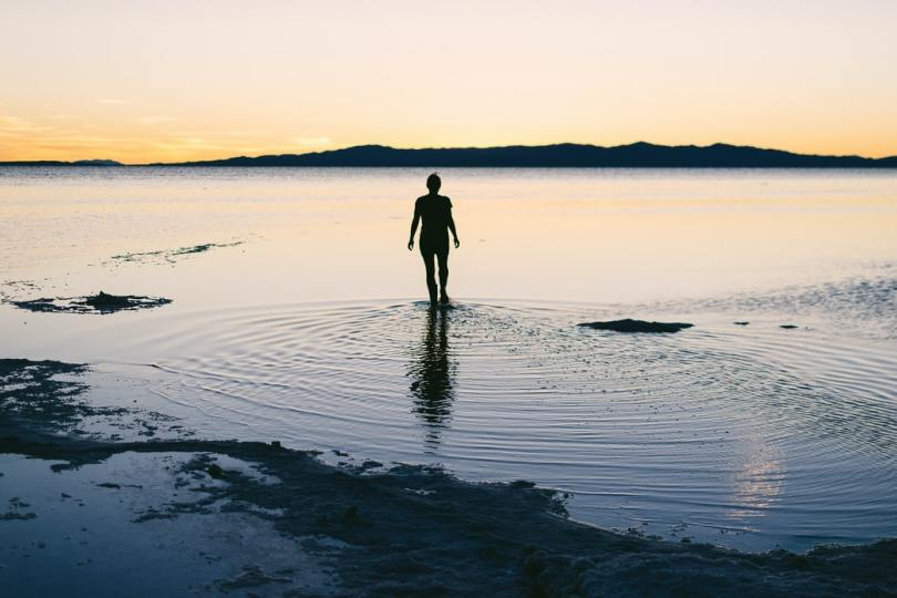 silhouette-of-person-standing-in-shallow-water-near-shore-at-sunset