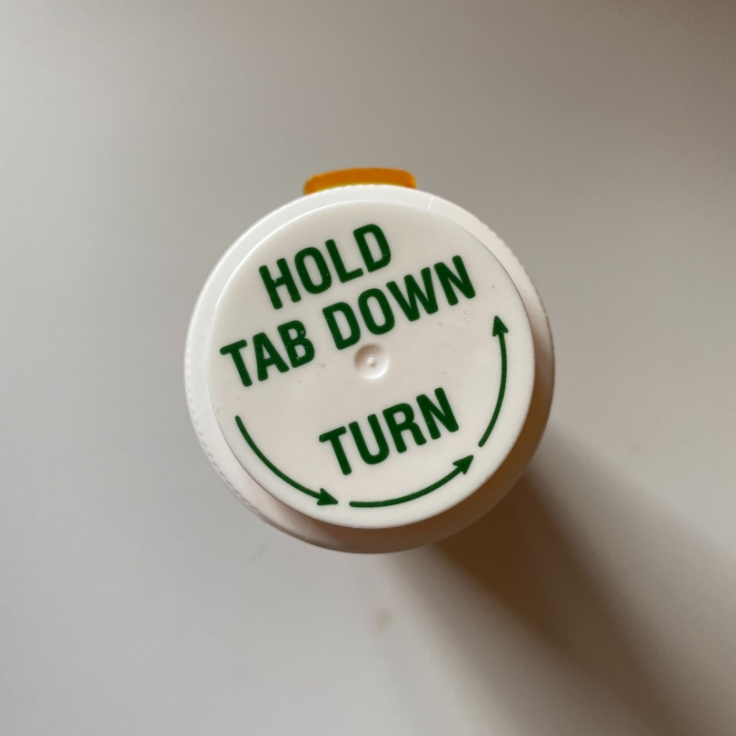 top-down-view-of-pill-bottle-with-tex-hold-tab-down-turn-with-arrows