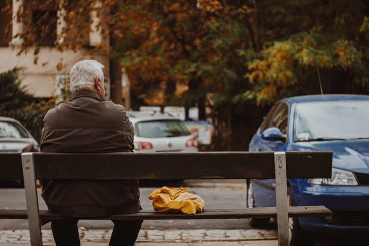 older-man-sitting-on-bench-near-parked-cars-viewed-from-behind