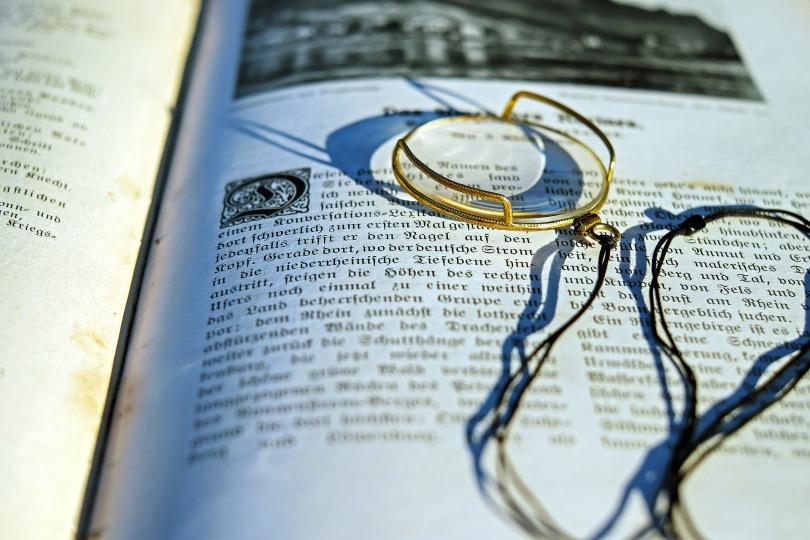 gold-monocle-resting-on-open-book-written-in-german