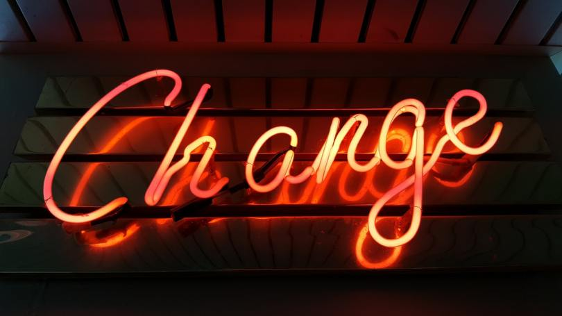 neon orange sign spelling change in cursive letters