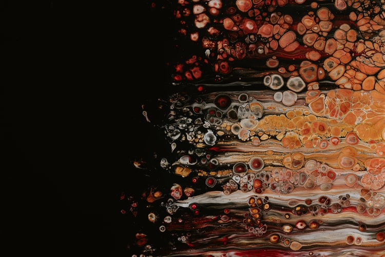 Abstract orange, red, and yellow paint bubbles on a black background