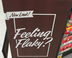 """A brown cardboard sign with white letters in cursive that say """"feeling flaky?"""""""