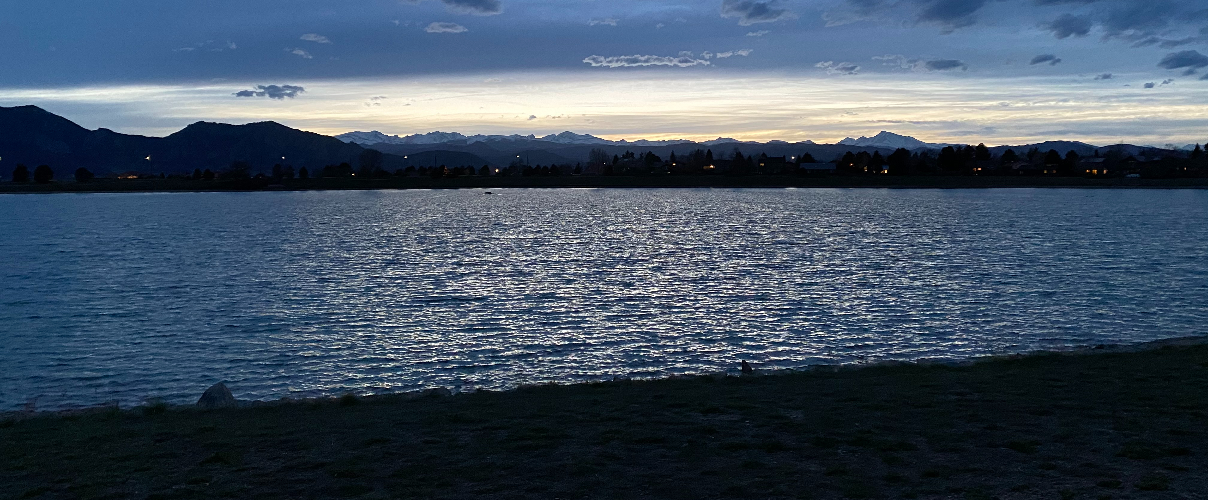 A blue lake with mountains in the background and a dark sky at night