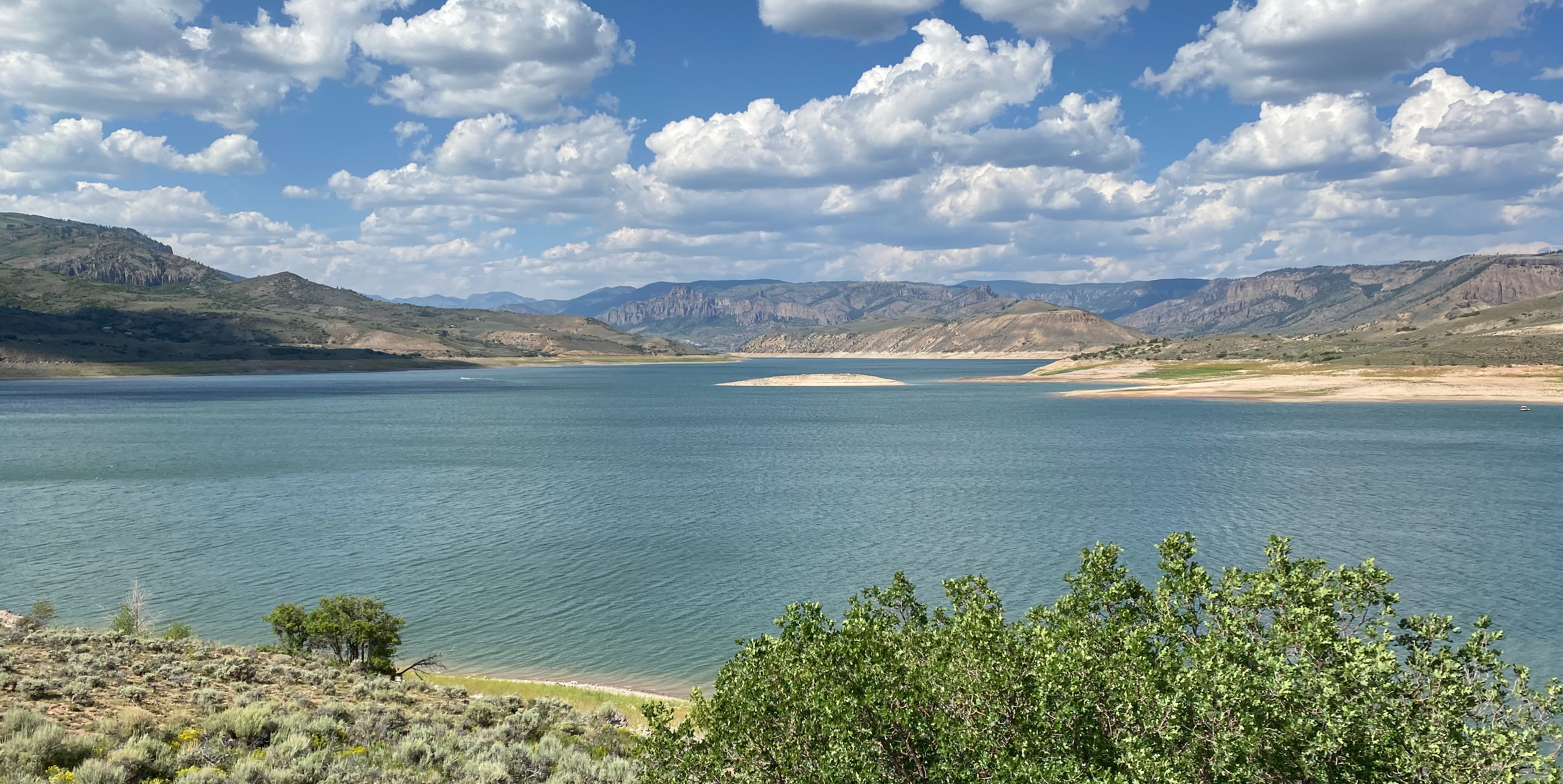 A sunny landscape with a large blue lake, green vegetation, mountains, and a blue sky with fluffy white clouds